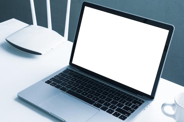 Computador portátil de tela em branco e dispositivo roteador em cima da mesa