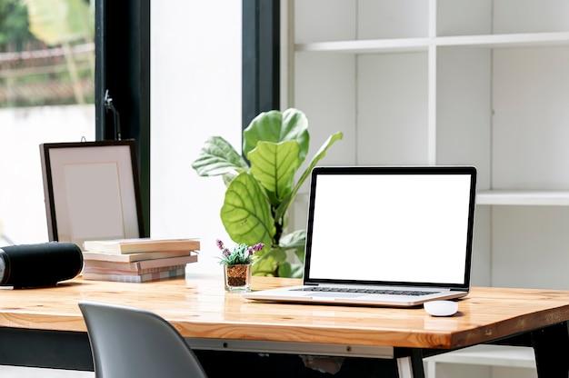 Computador portátil de tela em branco na mesa de madeira na sala de estar.