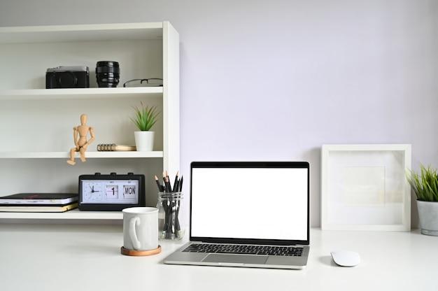 Computador portátil do modelo do maquilhador e caneca de café no espaço de trabalho.