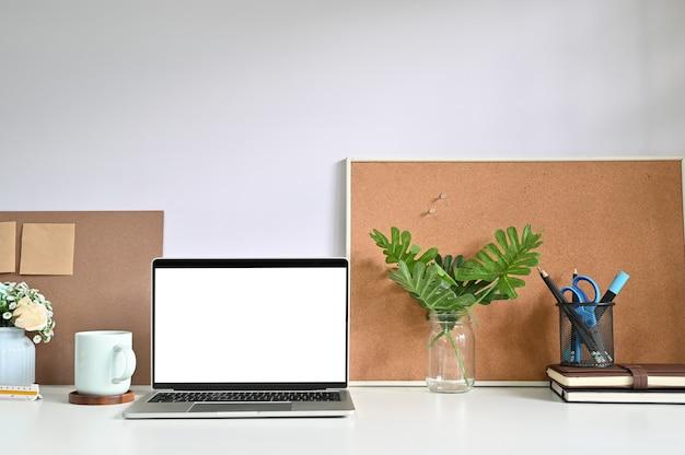 Computador portátil do modelo no espaço de trabalho e materiais de escritório.