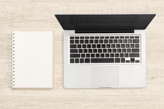 Computador portátil e caderno em branco na mesa de madeira.