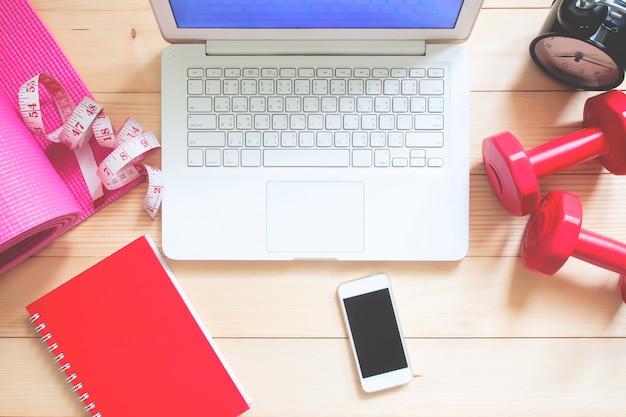 Computador portátil e dispositivo móvel na mesa de trabalho com equipamentos de fitness