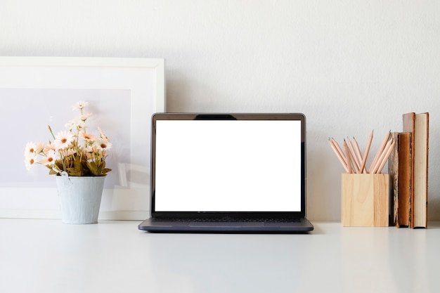 Computador portátil e flor do modelo no espaço de trabalho com copo e livro de café.