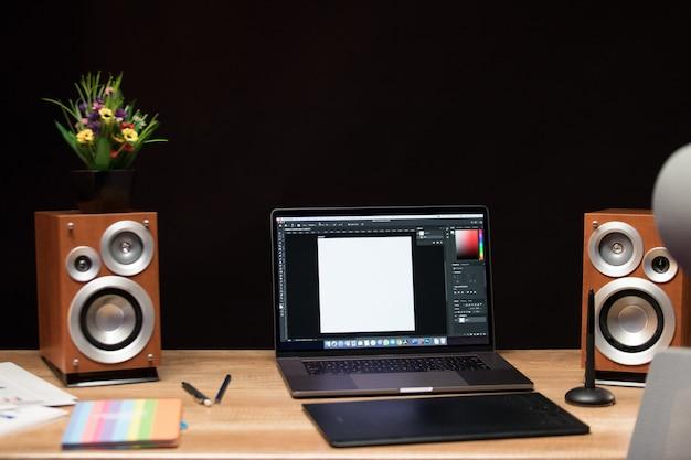 Computador portátil em cima da mesa com alto-falantes e flores