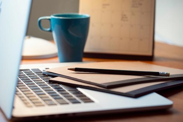 Computador portátil em uma mesa de negócios de madeira moderna com um bloco de notas e caneta.