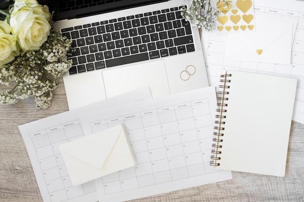 Computador portátil; flores; envelope; calendário e caderno espiral na mesa de madeira