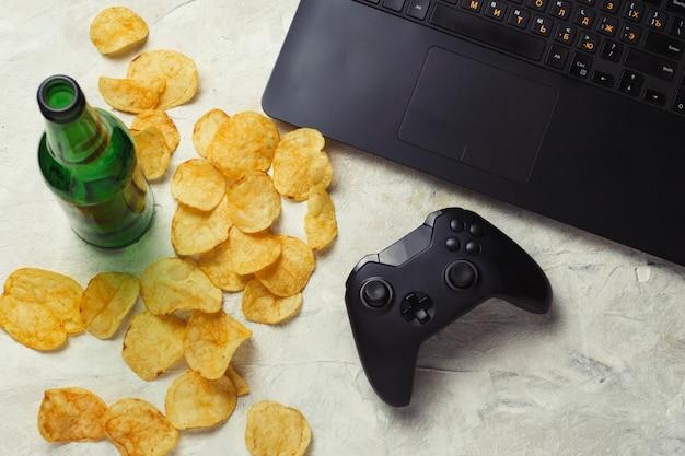 Computador portátil, gamepad, batatas fritas, garrafa de cerveja em uma superfície de pedra clara. conceito de jogos de computador e lazer