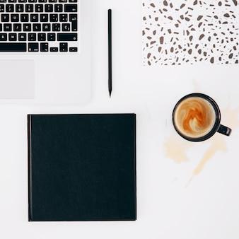 Computador portátil; lápis; caderno e copo de café derramado no fundo branco