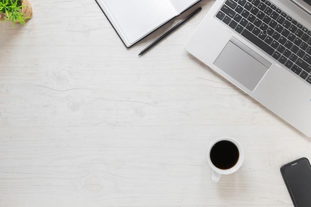 Computador portátil; lápis; diário; telefone celular e xícara de café na mesa de madeira texturizada