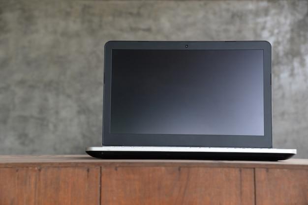 Computador portátil laptop com tela em branco na mesa de madeira