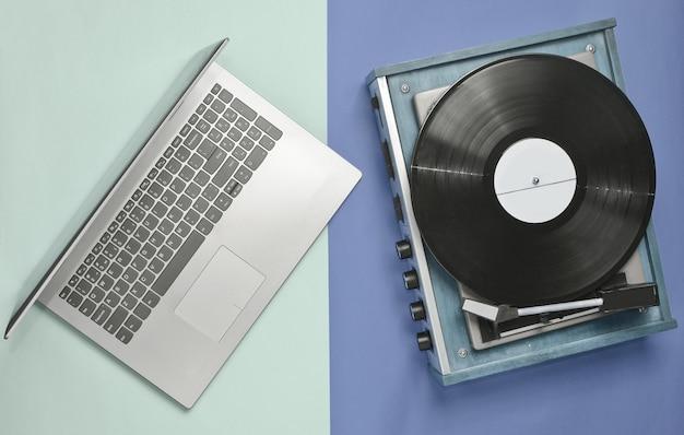 Computador portátil, leitor de vinil em um fundo colorido pastel