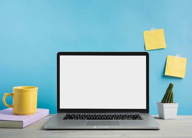 Computador portátil; livro e xícara de café na frente da parede azul