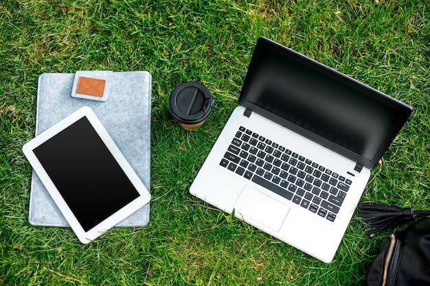 Computador portátil na grama verde com uma xícara de café, bolsa e tablet no parque ao ar livre. copie o espaço. natureza morta