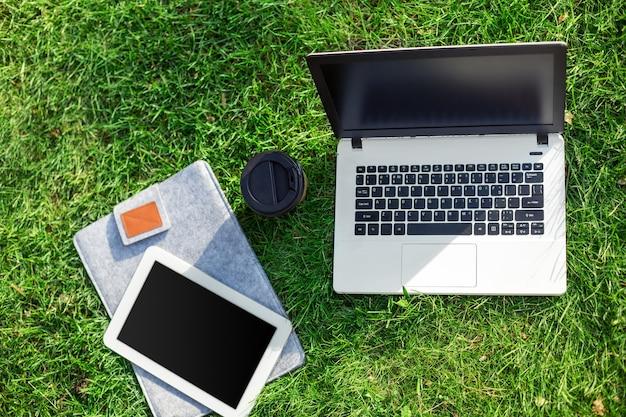 Computador portátil na grama verde com uma xícara de café e tablet no parque ao ar livre. copie o espaço. natureza morta