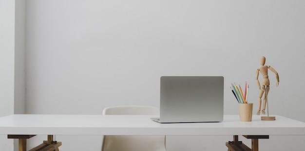 Computador portátil na mesa branca e xícara de café na sala de escritório moderno com parede branca