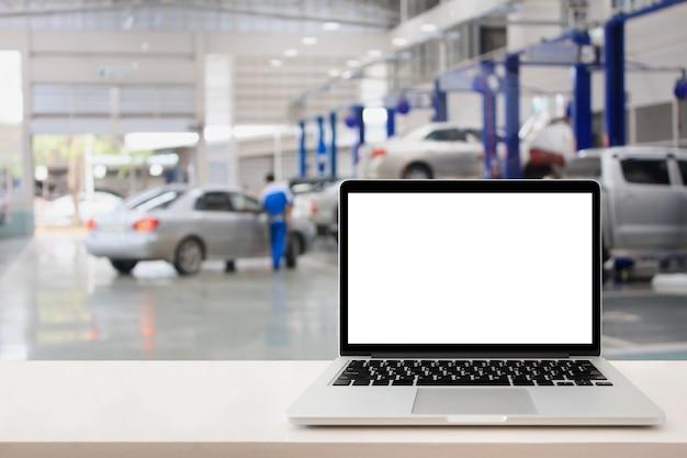 Computador portátil na mesa de madeira com fundo desfocado do centro de serviço automóvel