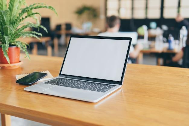 Computador portátil na mesa de trabalho com tela em branco simulada modelo.