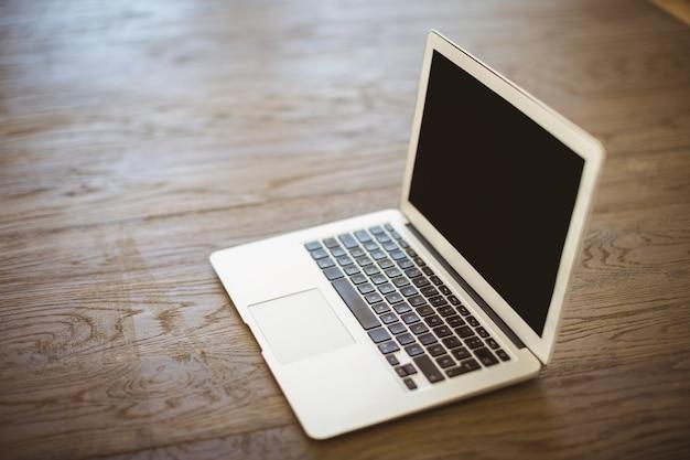 Computador portátil no chão de madeira