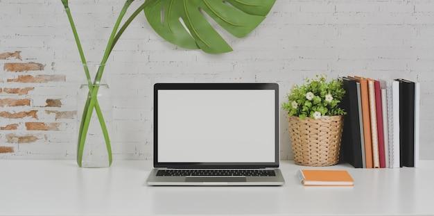 Computador portátil no local de trabalho de design confortável e material de escritório