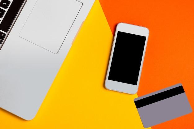 Computador portátil, smartphone com tela preta e cartão de crédito, vista superior