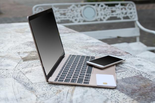 Computador portátil, smartphone e cartão de crédito