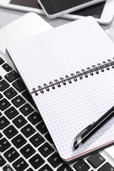 Computador portátil, smartphone, tablet, bloco de notas e caneta em cima da mesa