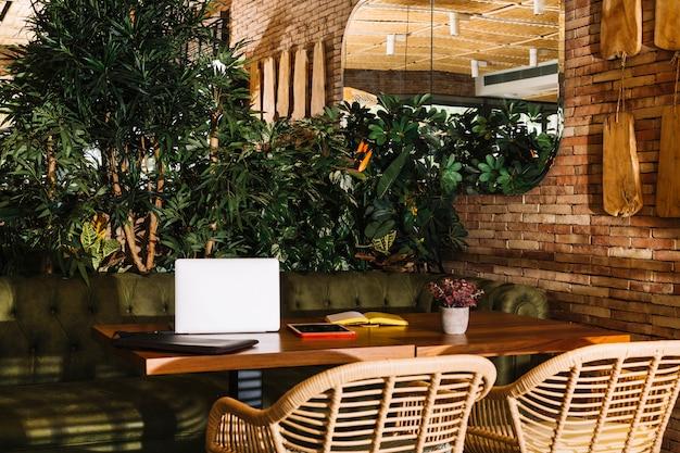 Computador portátil; tablet digital; livro e vaso de plantas na mesa de madeira no restaurante