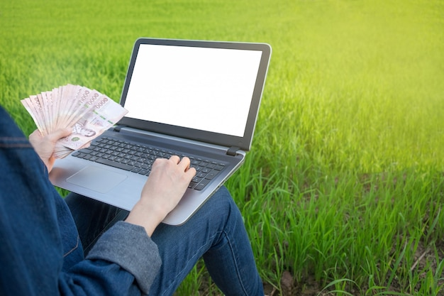 Computador portátil tela em branco e notas de dinheiro são realizadas pelo agricultor na fazenda de arroz verde