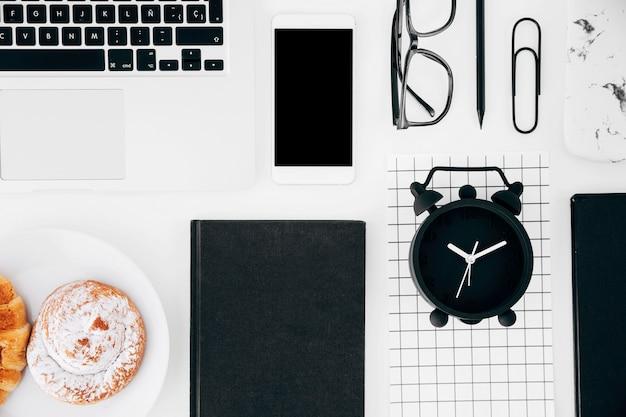 Computador portátil; telemóvel e tablet digital; óculos; lápis; pastelaria assada e página de despertador