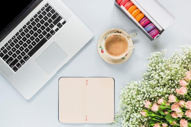 Computador portátil; xícara de café; bando de macaroons e flores sobre fundo branco