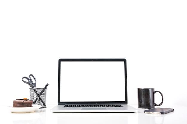 Computador portátil; xícara de café; telefone móvel e bolo no fundo branco