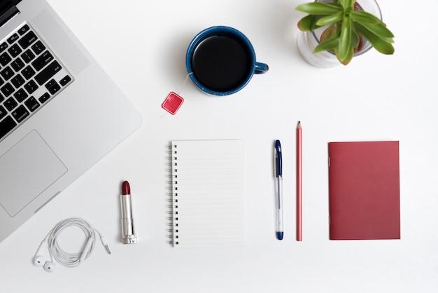 Computador portátil; xícara de chá; fone de ouvido; batom e papelaria do escritório na mesa branca