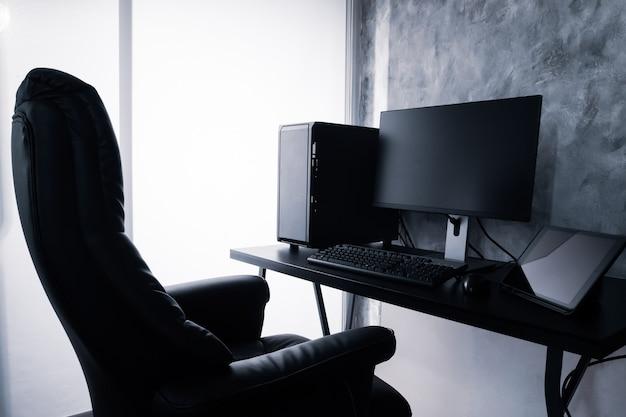 Computador preto e tablet na mesa.