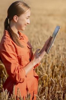 Computador tablet agrônomo mulher caucasiana, tecnóloga, no campo de trigo, verificando a qualidade