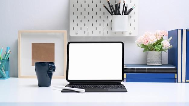Computador tablet com tela vazia, livros e material de escritório na mesa branca