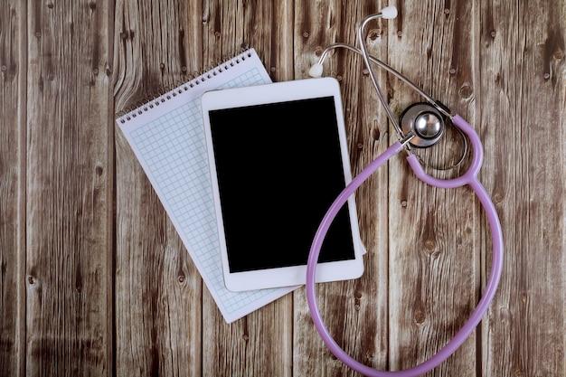 Computador tablet digital com estetoscópio médico na mesa de mármore no hospital do consultório médico