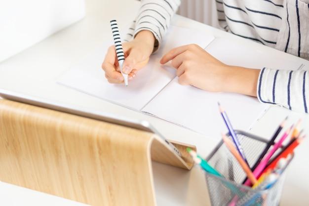 Computador tablet digital e mãos de criança escrevendo dever de casa no caderno com caneta