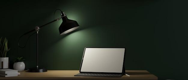 Computador tablet digital em maquete de tela em branco sob luz fraca do abajur escritório de trabalho escuro