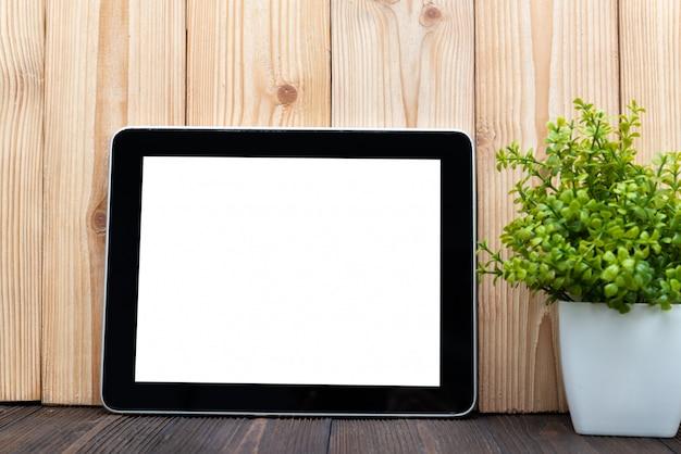 Computador tablet em branco e pequena árvore na madeira