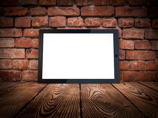 Computador tablet em tijolos e madeira