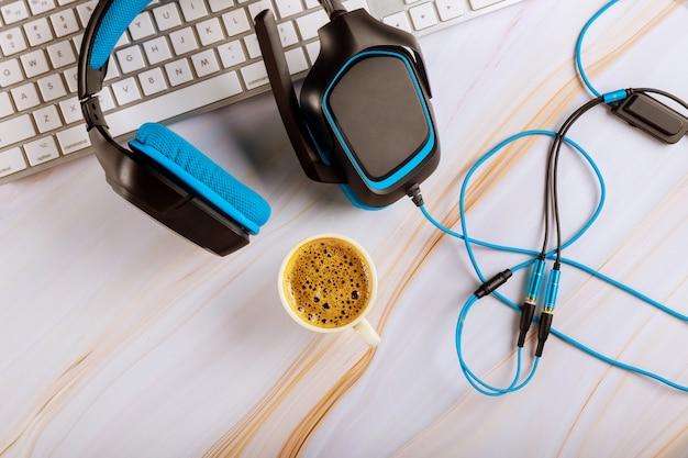 Computador teclado branco com fone de ouvido em um telefone de suporte ao cliente, trabalhando na mesa de escritório de call center com xícara de café Foto Premium