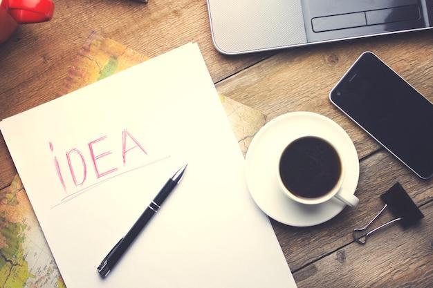 Computador, telefone inteligente, xícara de café, papel e caneta na mesa de madeira