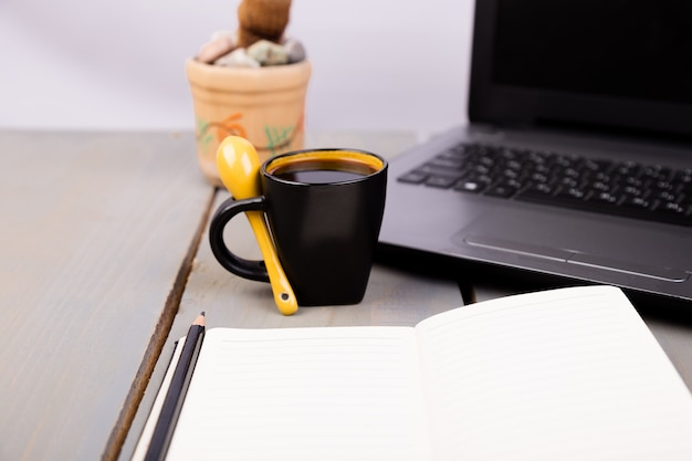 Computador, xícara de café, cacto e notebook na madeira