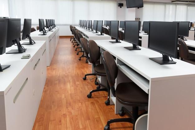 Computadores de sala de aula. não esvazie nenhum pessoa com muitos monitora o computador na mesa branca.