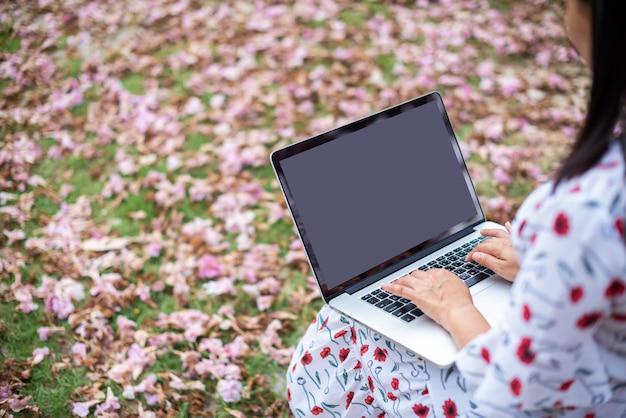 Computadores portáteis no regaço da mulher com flores cor-de-rosa e fundo da grama verde.