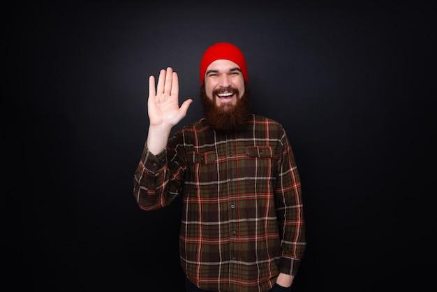 Comum amigável e feliz barbudo jovem acenando com a mão levantada em olá gesto sorrindo como saudação dizendo oi sobre parede escura