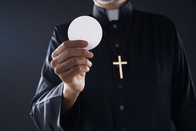 Comunhão wafer hostia padre nas mãos