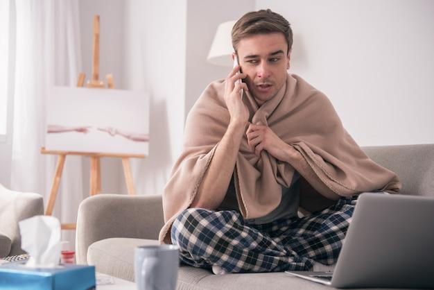 Comunicação à distância. homem doente e infeliz sentado em casa enquanto falava com o amigo