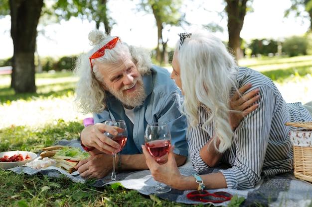 Comunicação agradável. casal simpático encantado tomando um vinho enquanto tem uma conversa agradável