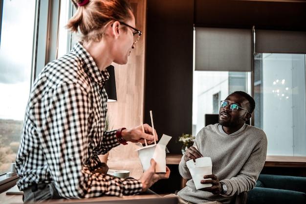 Comunicação agradável. homem alegre sentado em posição semi-aberta, segurando uma caixa de papel com o jantar